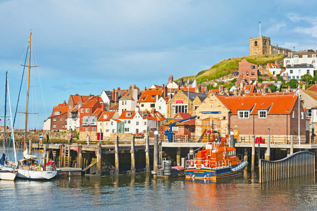 Whitby in Yorkshire with yachts and Saint Mary's Church in the background.
