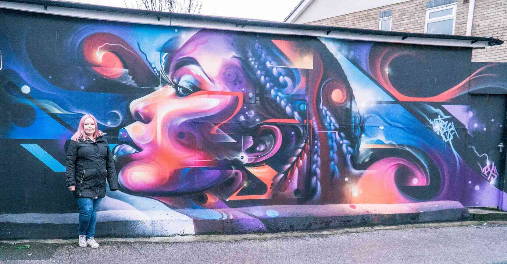 Kat standing in front of Penge Street Art