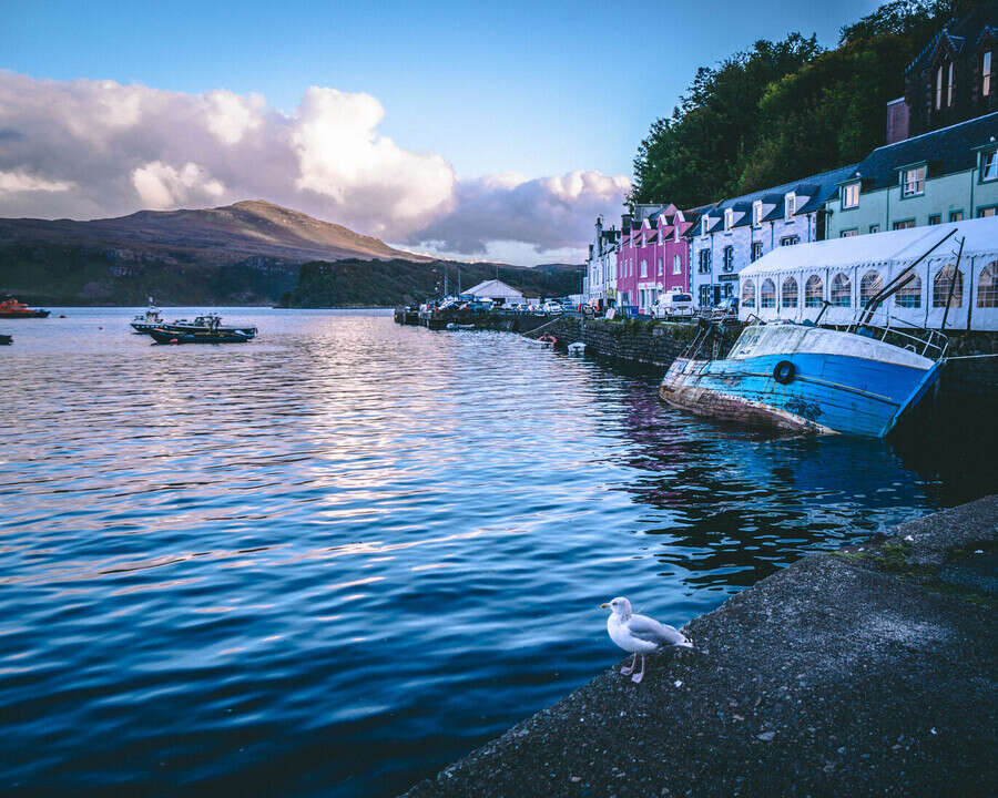 View from Portree over the sea with the colourful houses and a boat