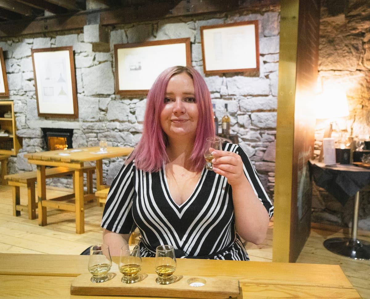 Kat drinking whisky at Oban Distillery