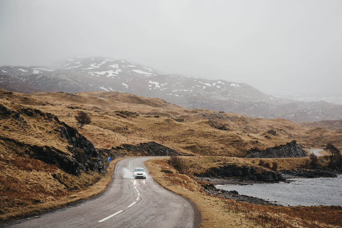 Unidentified car driving on a road going through Scottish Highlands near Lochinver