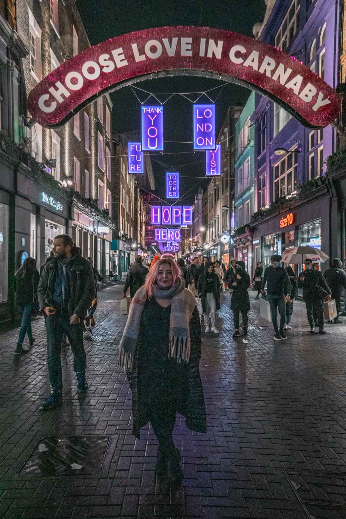 Kat standing in front of the choose love in Carnaby Christmas lights