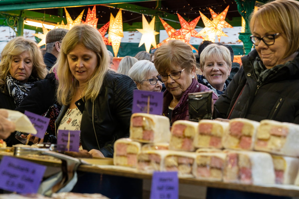 Women Shoppers looking at cakes on a stand at a Christmas Market in Harrogate, England Credit_Steve Gill
